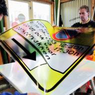 De bebordingsklus voor de atoomtop is de grootste klus van het jaar voor Traffic Service Nederland in Badhoevedorp, zegt bedrijfsleider Peter Hoen. In het kantoor zoeven de printers en plotters, maar die doen dat ook bij de andere negen vestigingen in Nederland. In de werkplaats wordt secuur geplakt op de bekende gele borden.